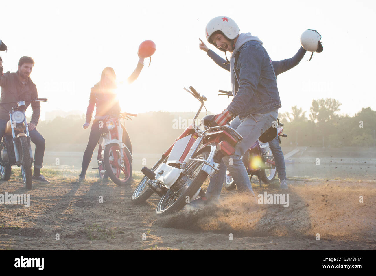 Small group of friends sitting on mopeds, holding crash helmets in air - Stock Image