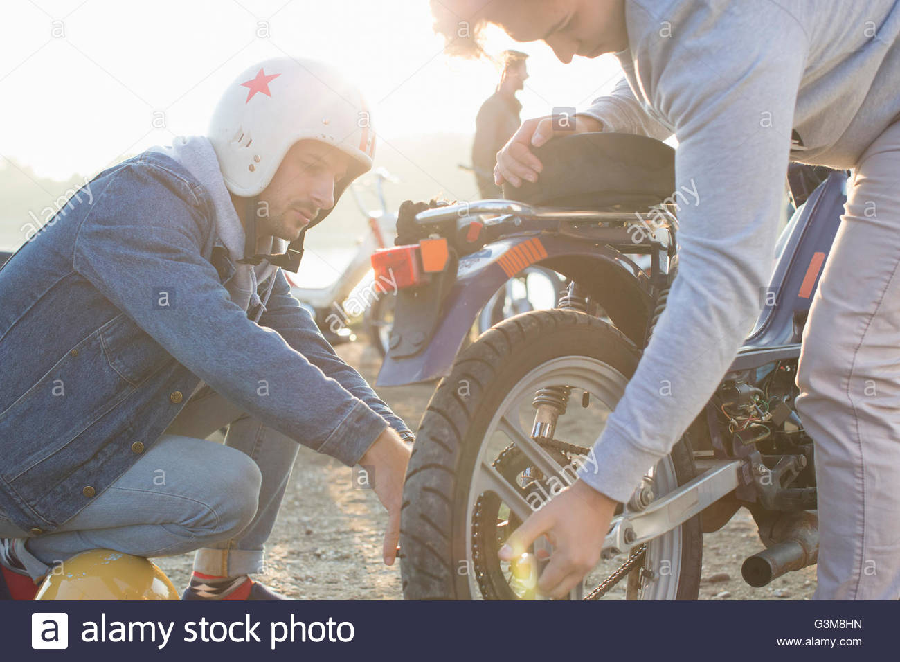 Two men fixing wheel on moped, outdoors - Stock Image