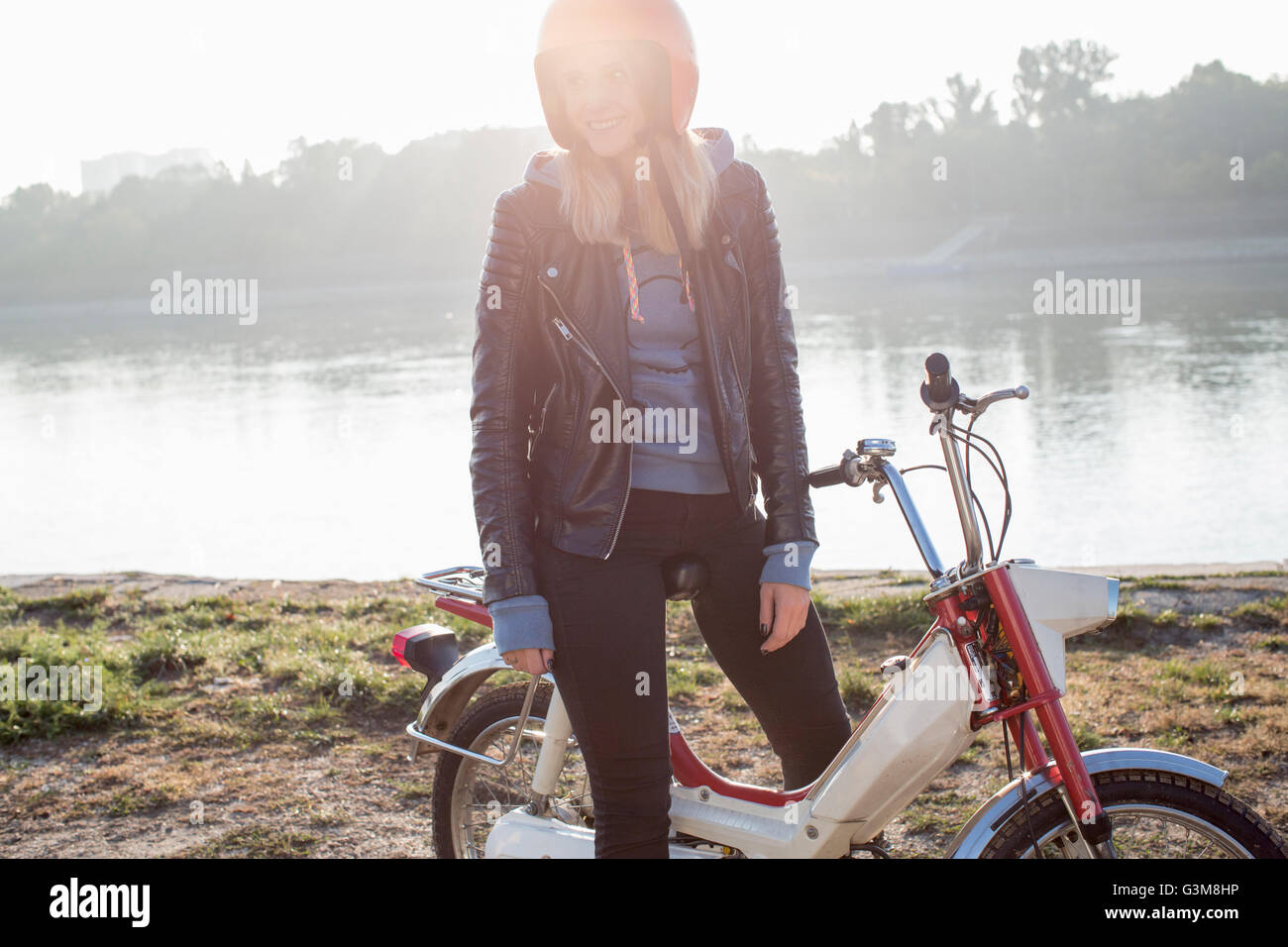 Young woman sitting on retro moped, beside lake - Stock Image