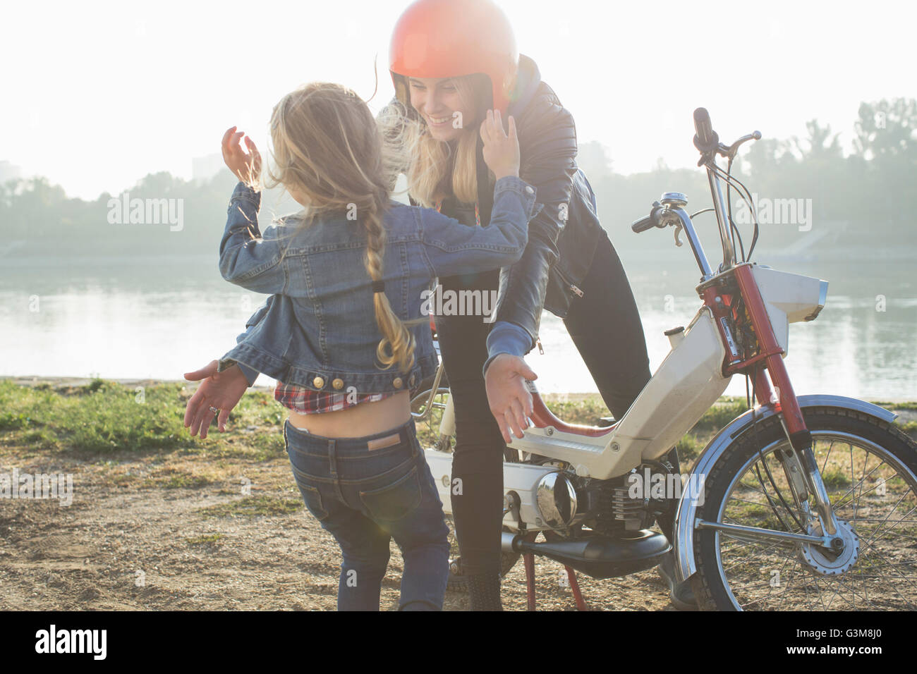 Young woman sitting on retro moped, daughter running towards her - Stock Image