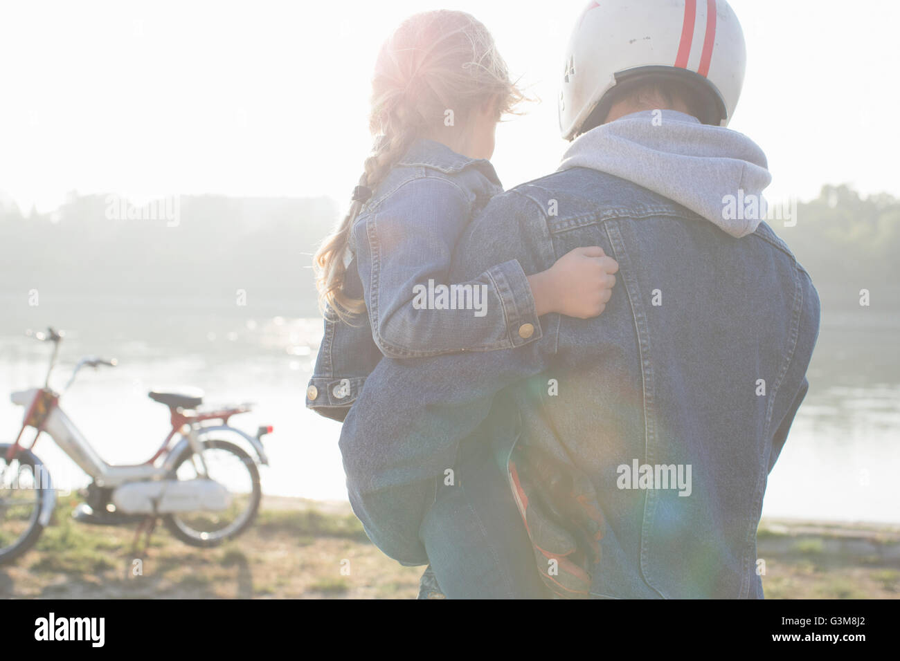 Father holding daughter, beside lake, father wearing crash helmet, rear view - Stock Image