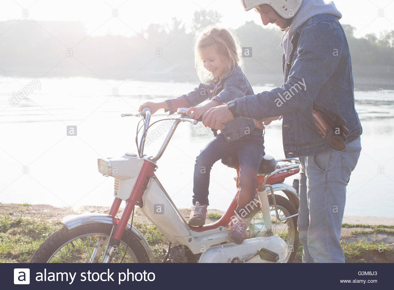 Young girl sitting on father's moped, father standing beside her, beside lake - Stock Image