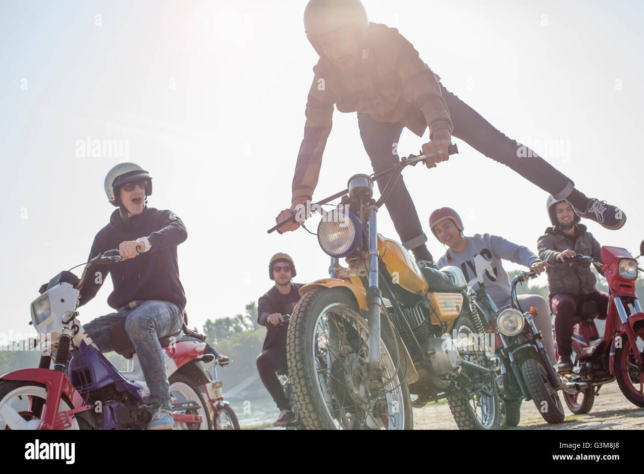 Group of friends riding mopeds along road, man in mid air, doing stunt - Stock Image