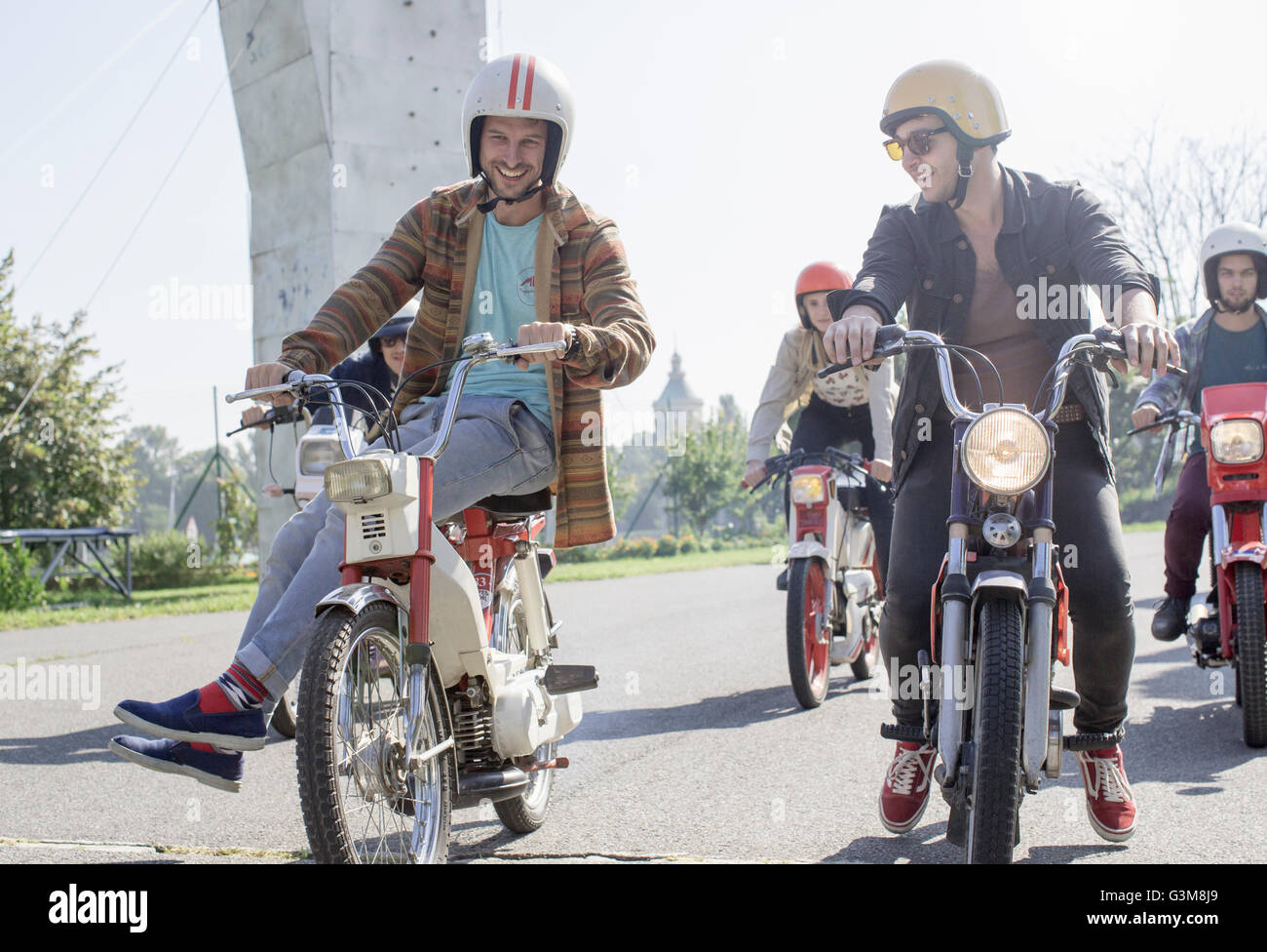 Group of friends riding mopeds along road - Stock Image