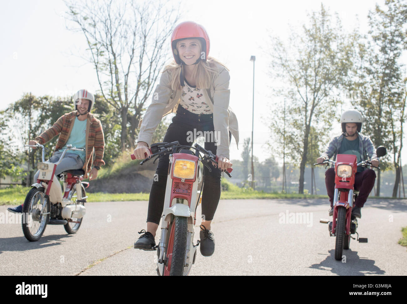 Group of friends riding mopeds along road, young female rider in foreground - Stock Image