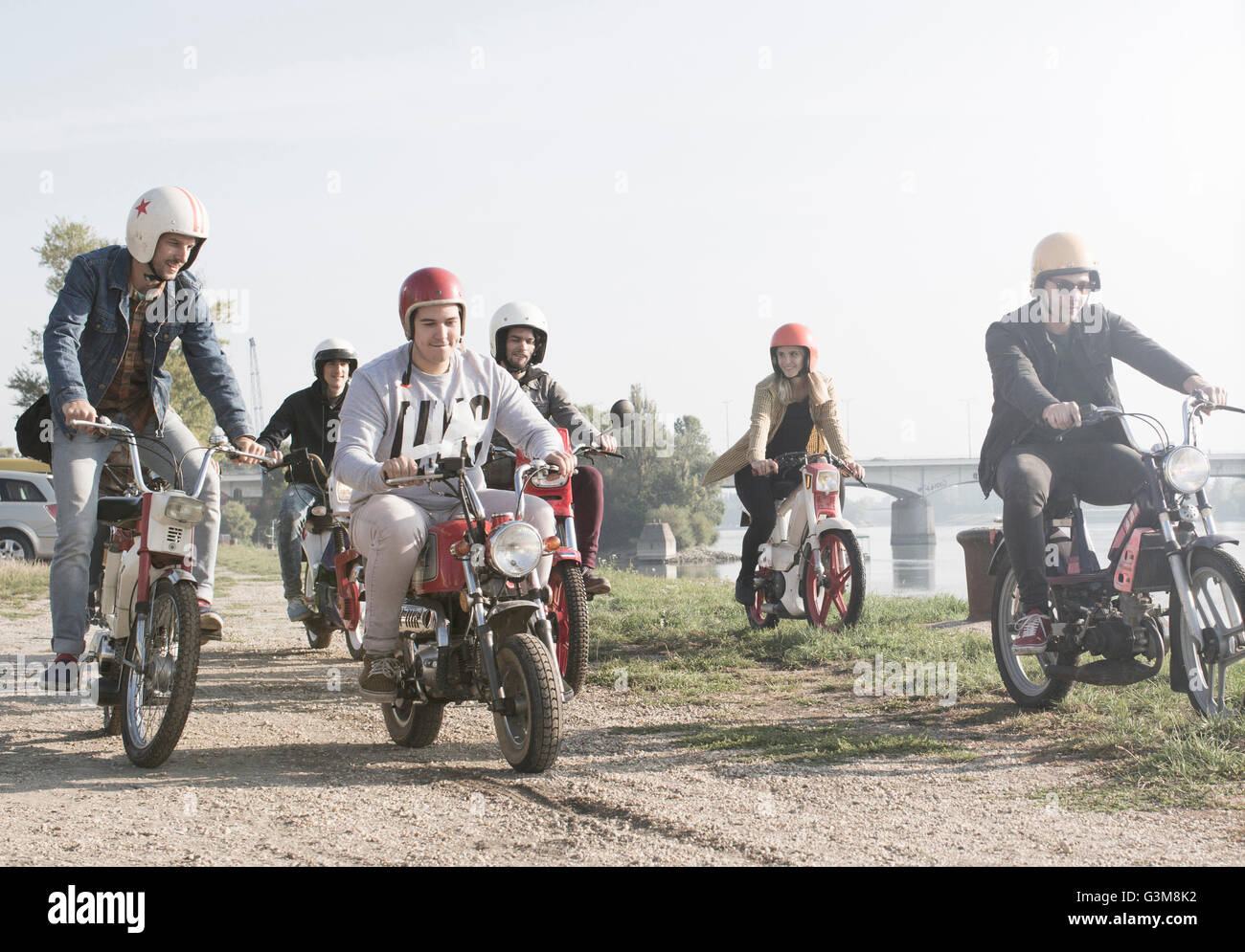 Group of friends riding mopeds beside lake - Stock Image
