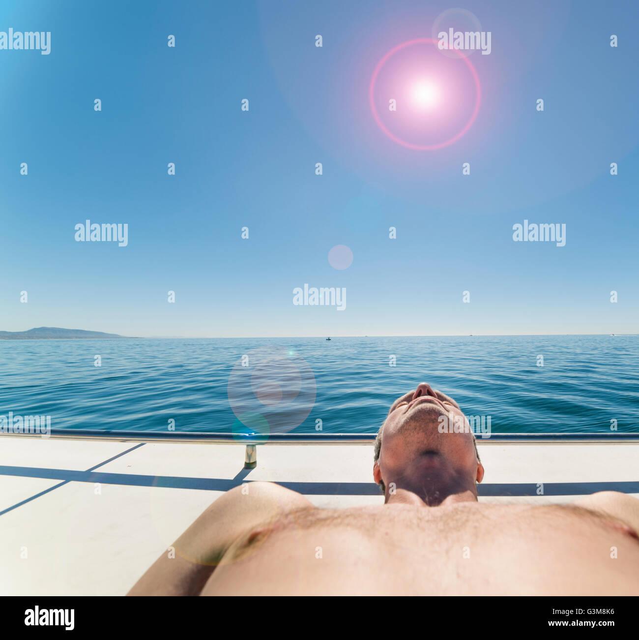 Man on sailboat sunbathing - Stock Image