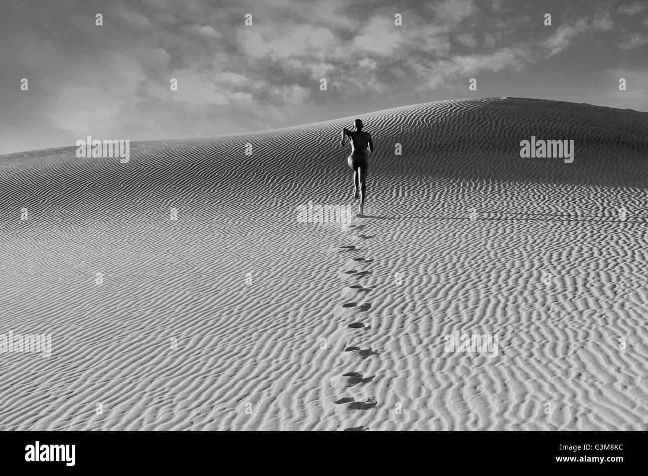 Nude woman running in dessert leaving footprints - Stock Image