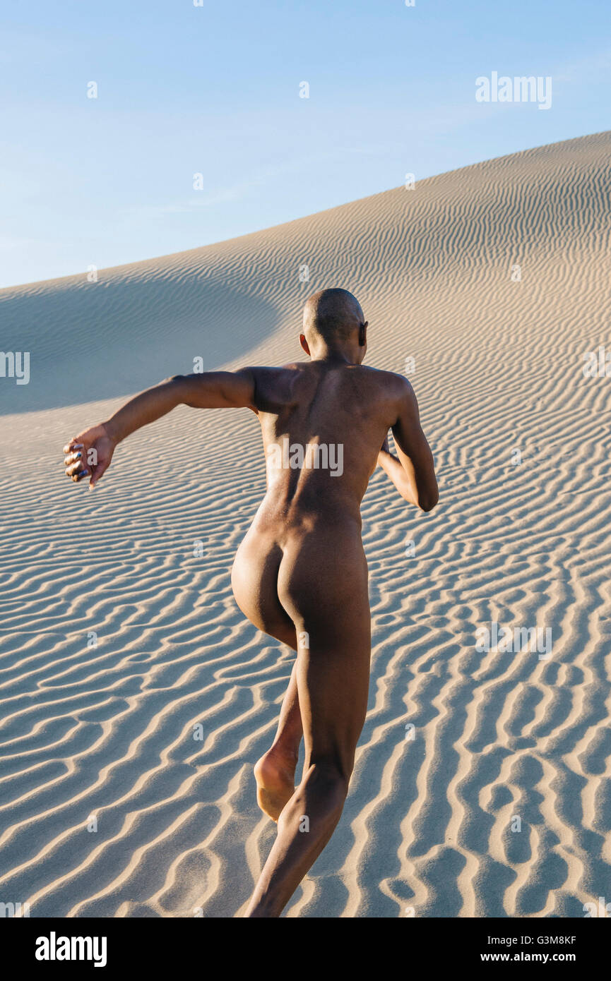 Rear view of nude woman in dessert running - Stock Image