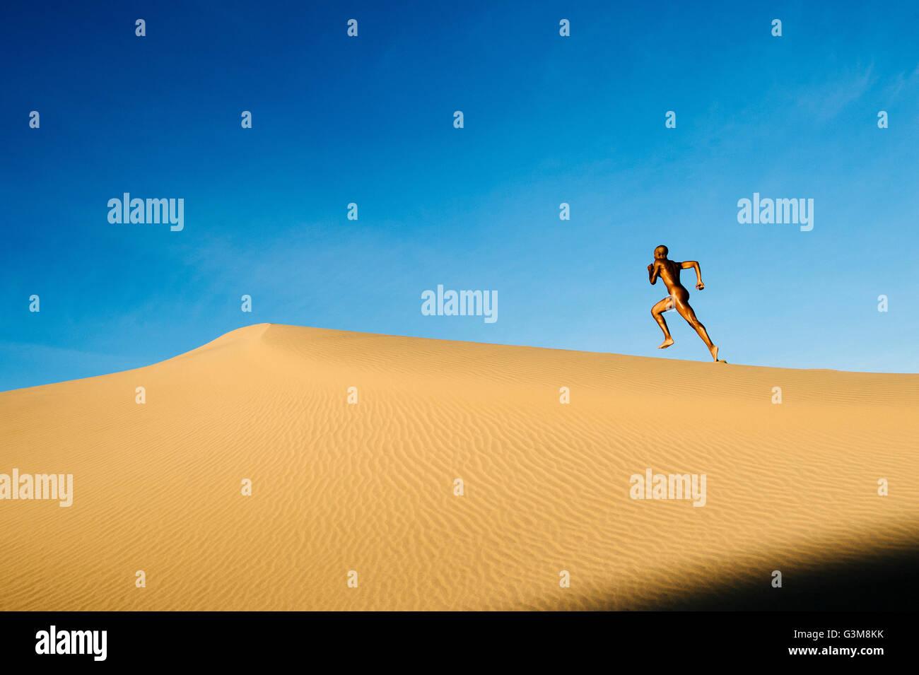 Nude woman in desert running on dune - Stock Image