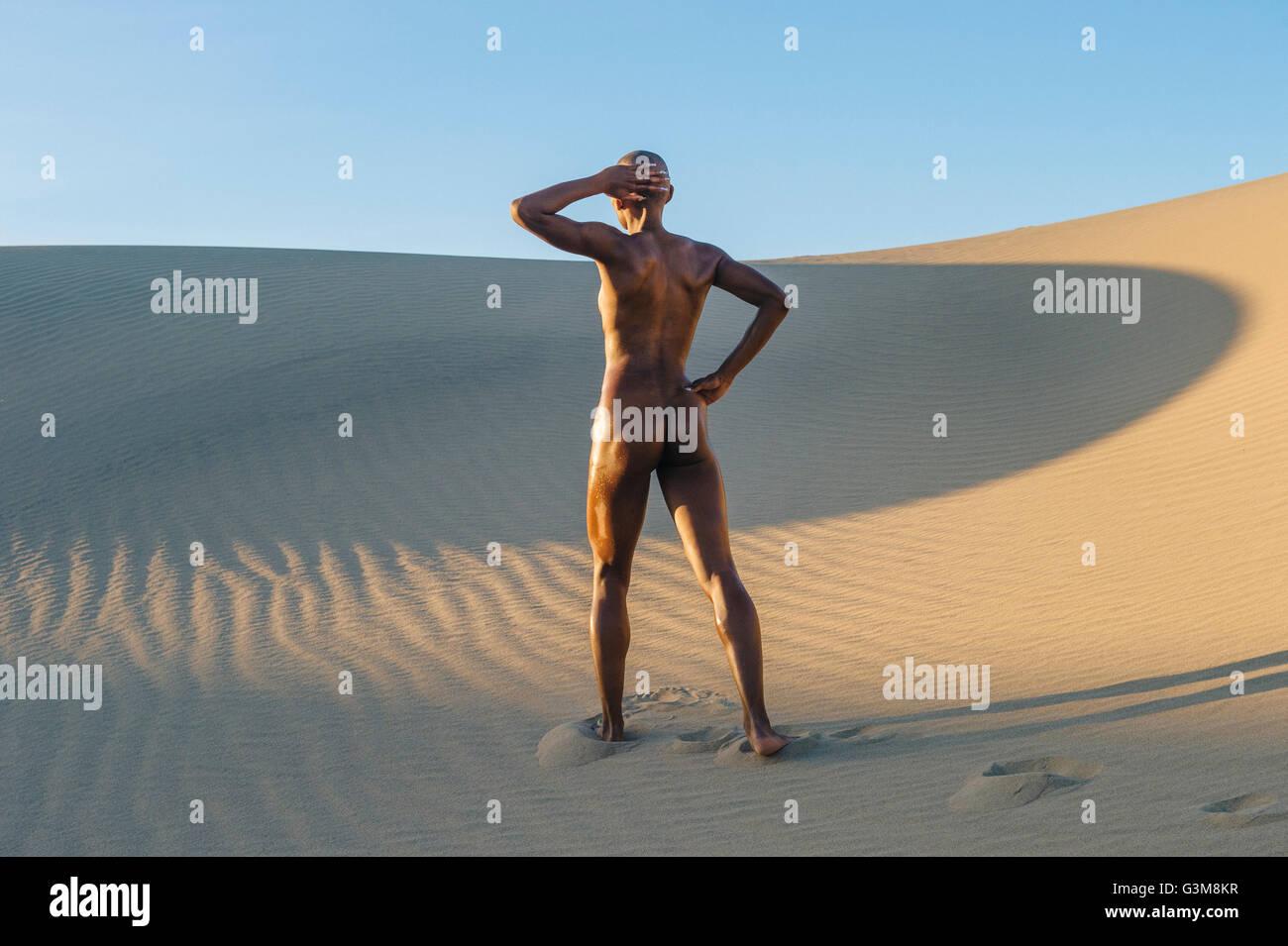 Nude woman standing in desert - Stock Image