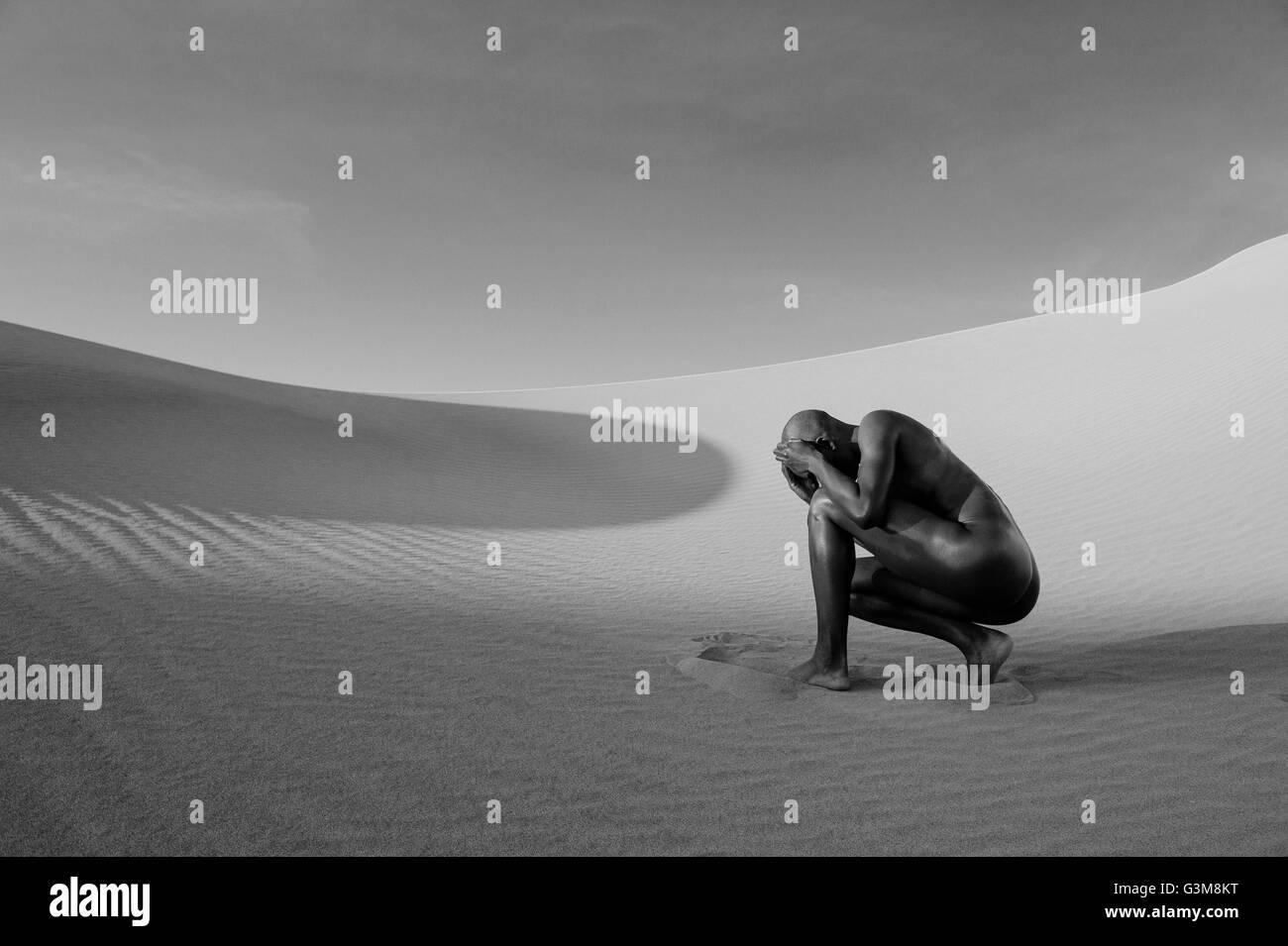 Nude woman cowering in desert - Stock Image