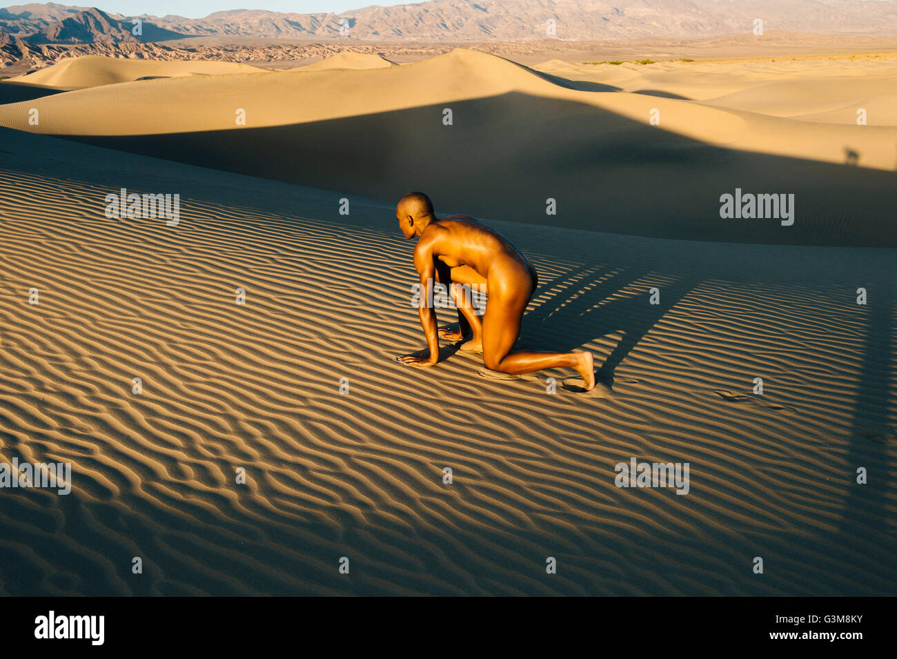 Nude woman in start position in dessert - Stock Image