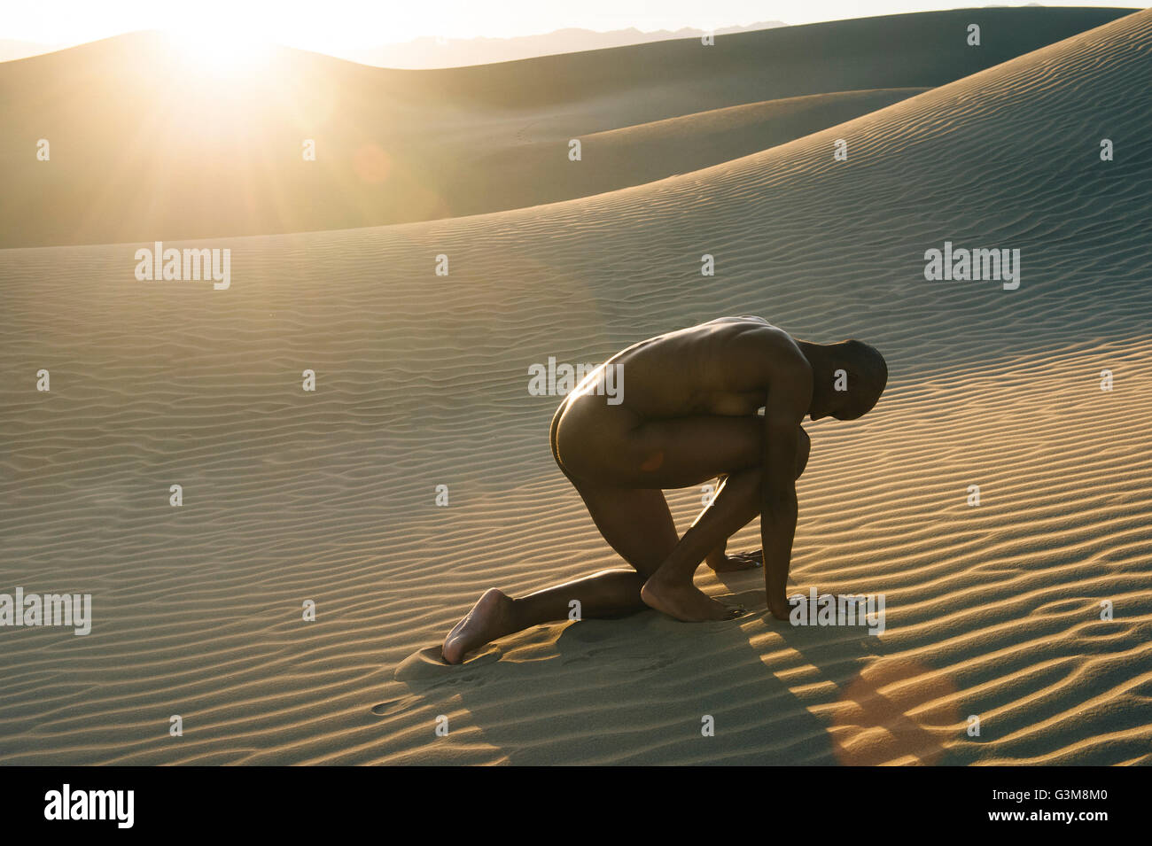 Nude woman crouched in the desert - Stock Image