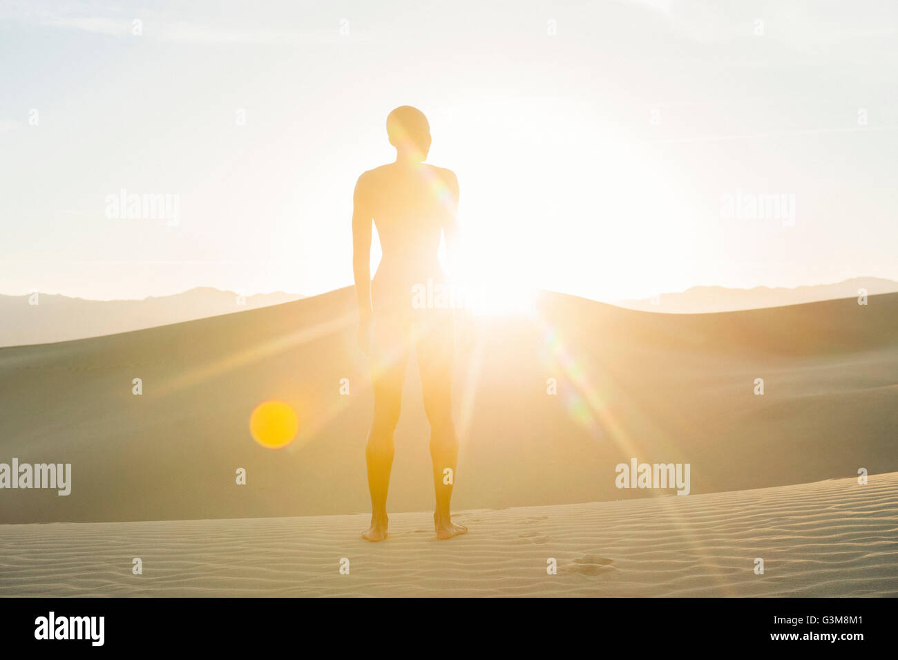 Nude woman in desert standing on dune in sunlight - Stock Image
