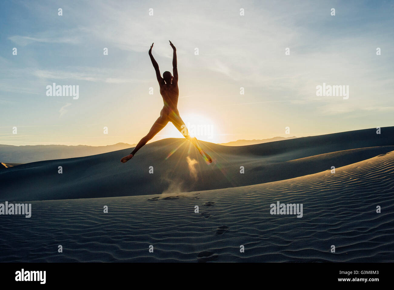 Nude woman in desert arms raised jumping in mid air - Stock Image