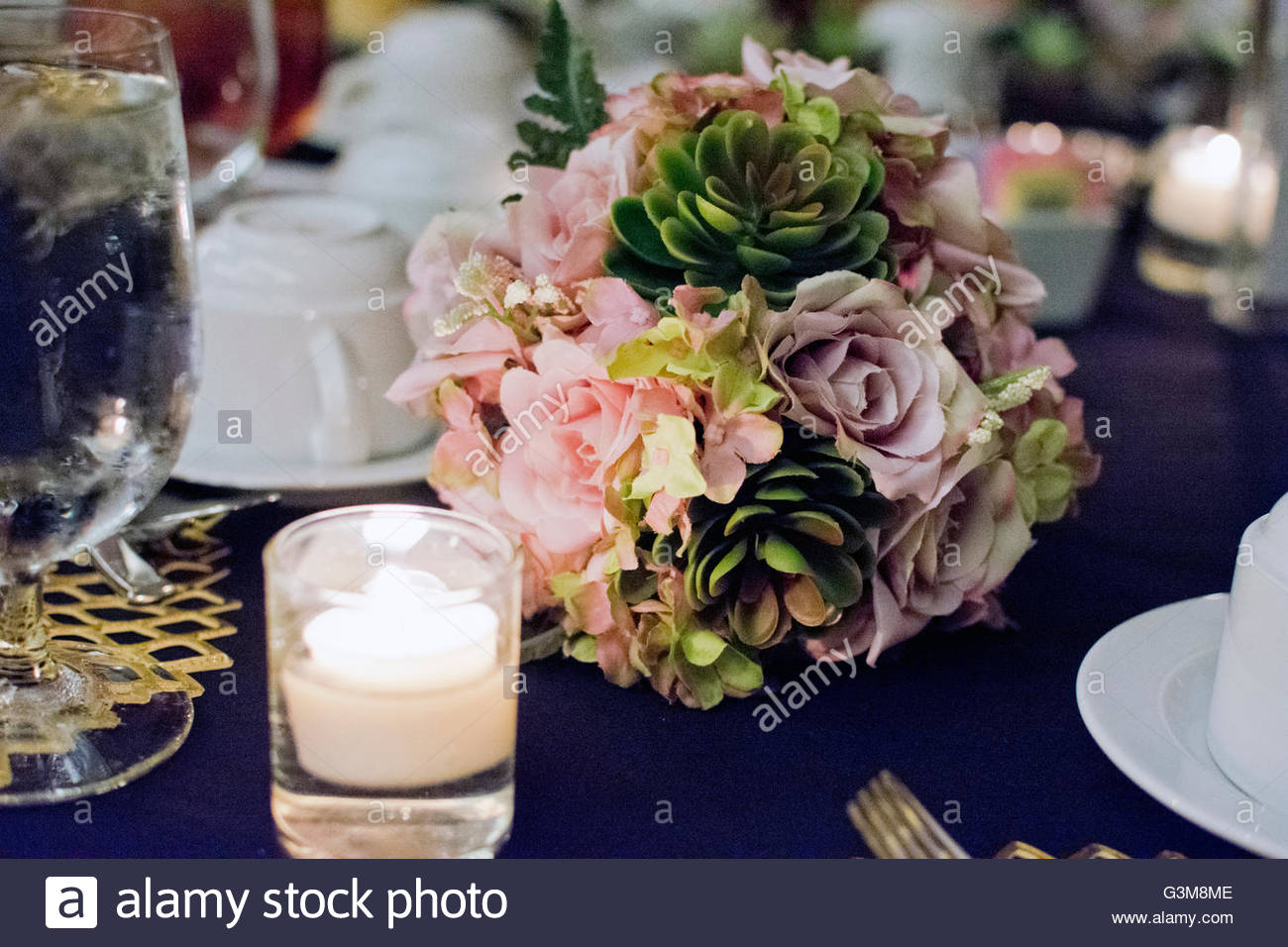 Prepared wedding reception table with flower arrangements and candlelight - Stock Image