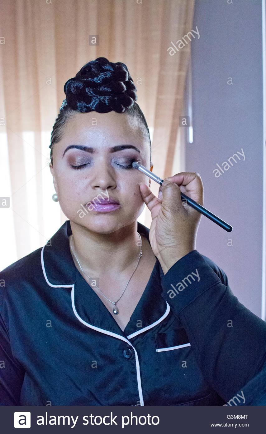 Bride having eyeshadow applied in hotel room - Stock Image