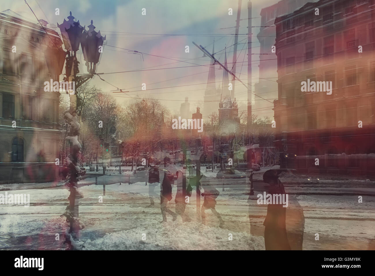 Reflection of snow-covered streets with lanterns and houses of Riga in a poster in the window of the Latvian National - Stock Image