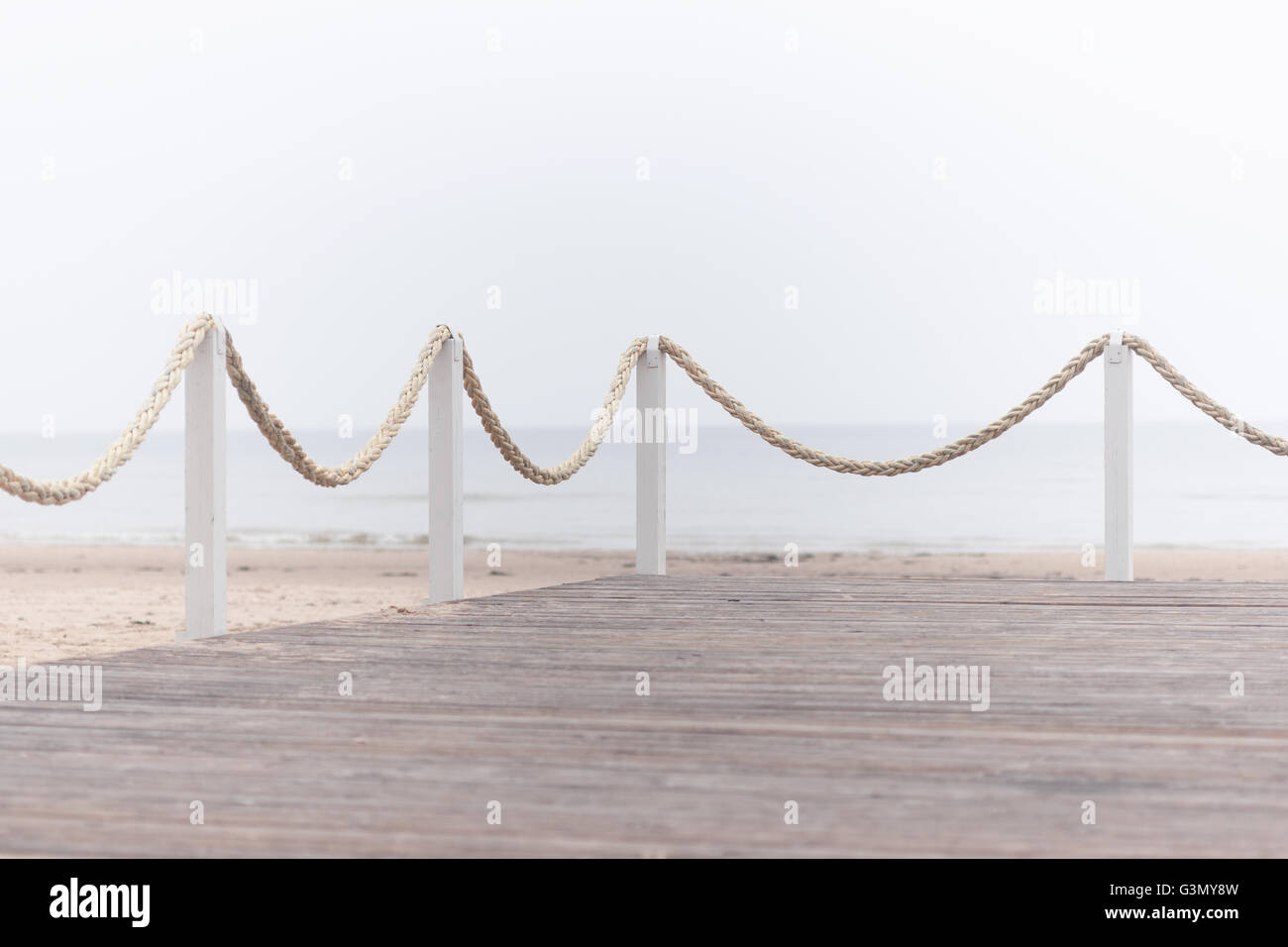 White rope on poles on a wooden platform on the sandy beach of the Baltic Sea on the background of the sea in the - Stock Image