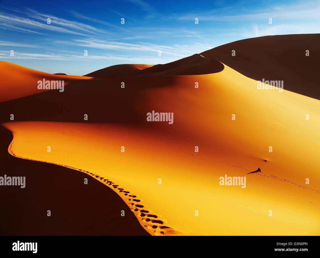 Sand dune with footprints at sunrise, Sahara Desert, Algeria - Stock Image