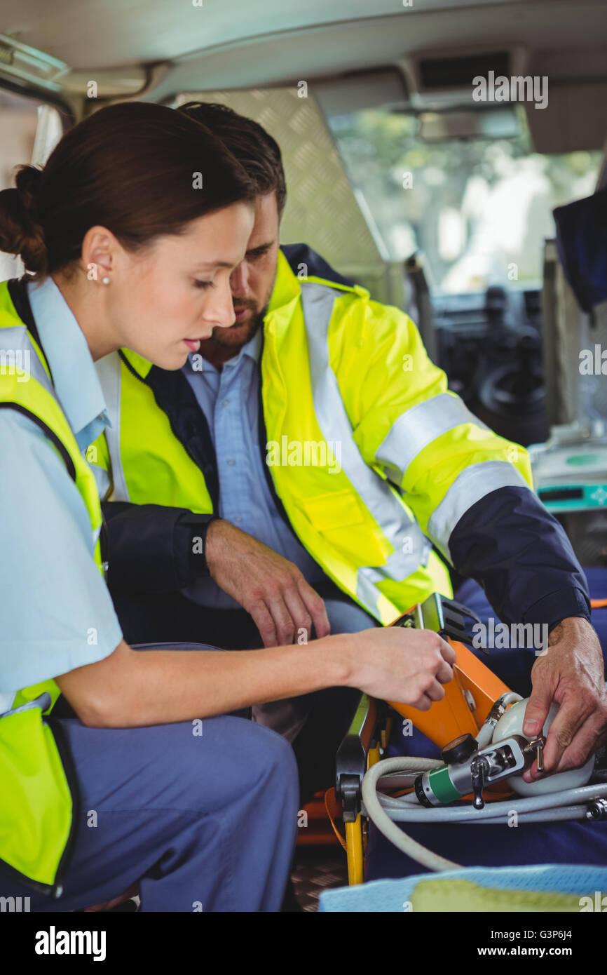 Ambulance crew adjusting an equipment - Stock Image