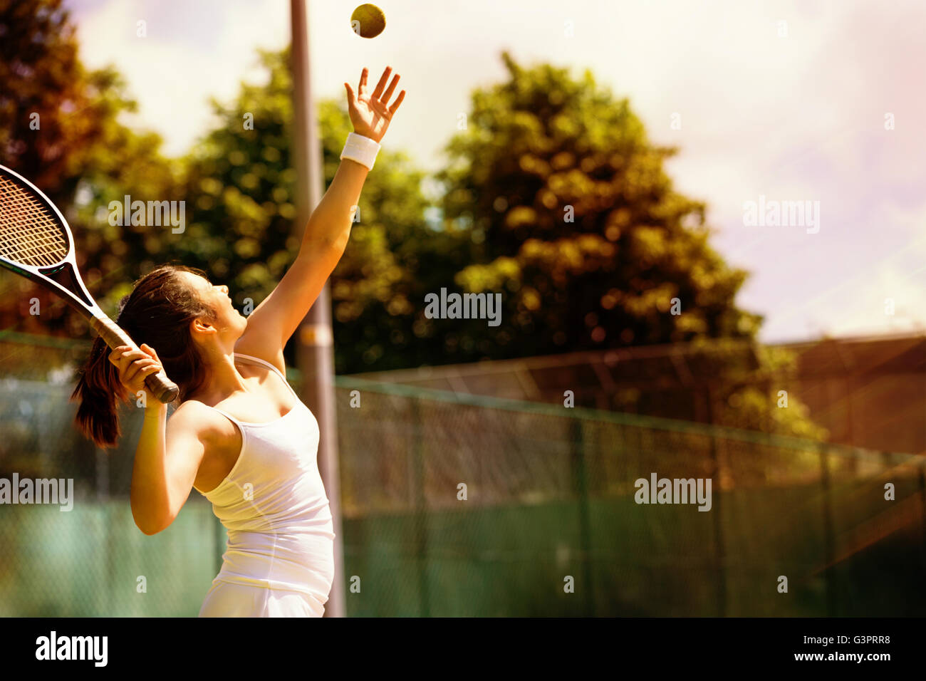 Rear view of tennis player serving - Stock Image