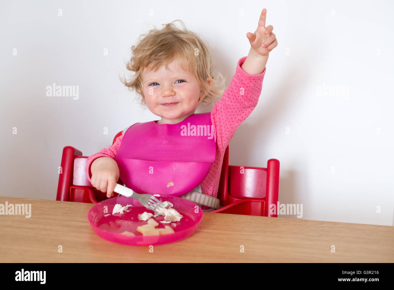 One year old baby sitting in high chair and eating meal, England, UK