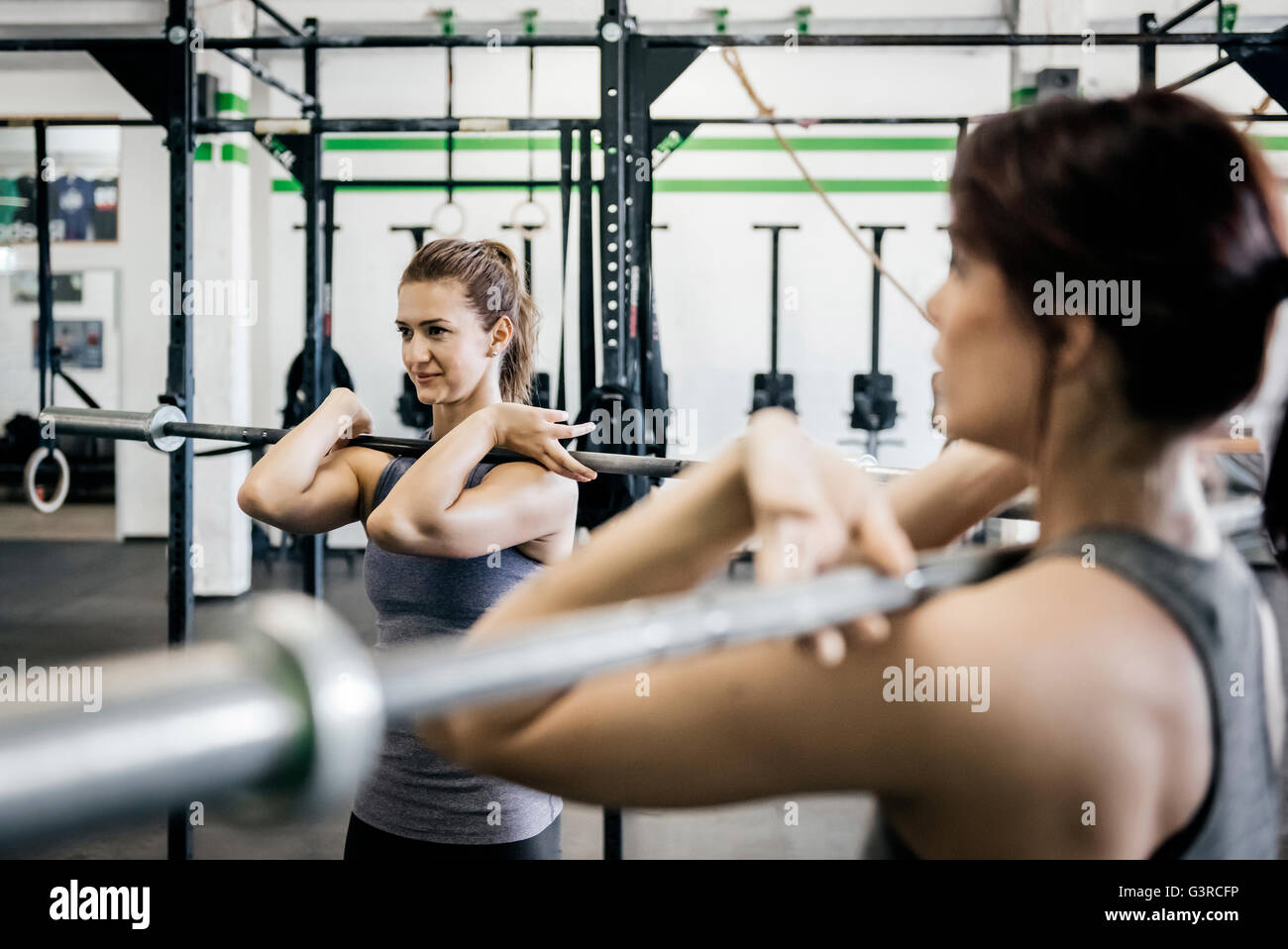 Germany, Two young women weightlifting in gym - Stock Image