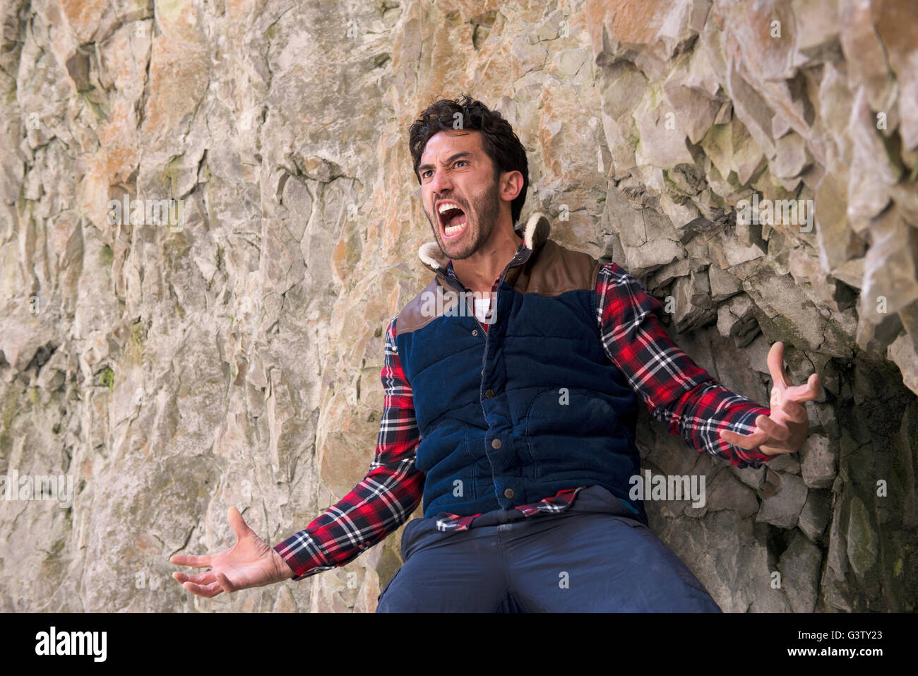 A climber with an angry expression standing on a ledge in rugged terrain. - Stock Image