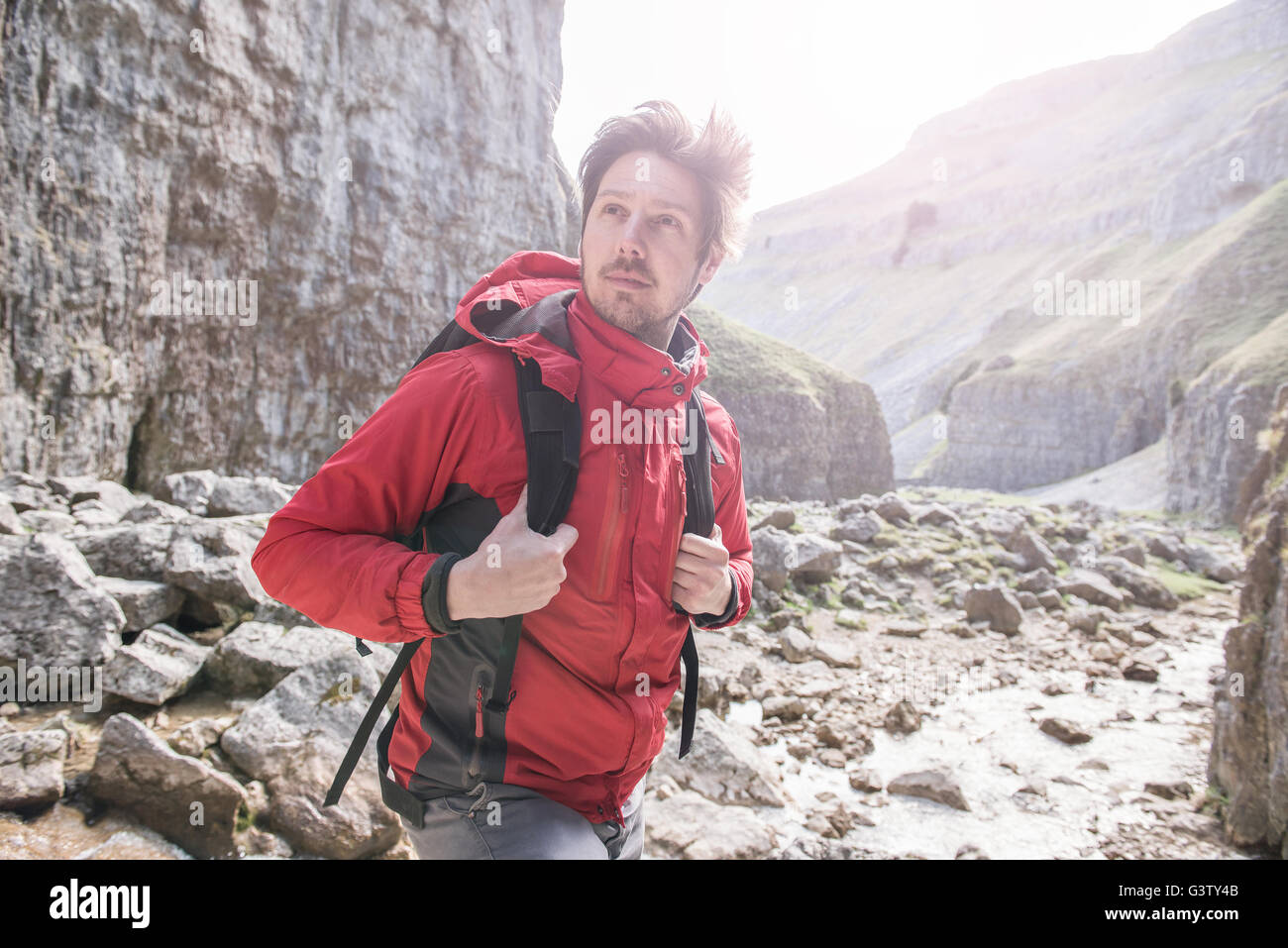 A climber with a rucksack standing in rugged terrain. - Stock Image