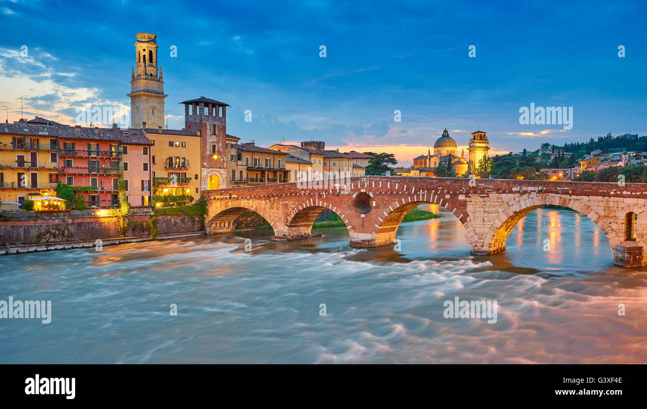 Ponte Pietra Bridge at evening dusk, Verona old town, Veneto region, Italy - Stock Image