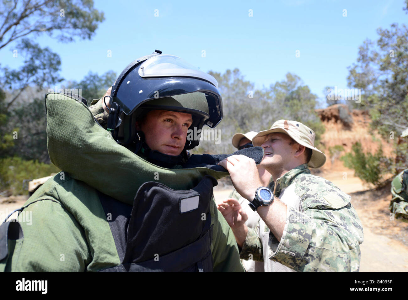 Soldier provides assistance in putting on a bomb suit. - Stock Image