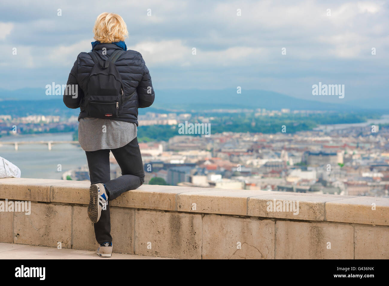 A tourist surveys the centre of Budapest from the top of Gellert-hegy (hill) on the Buda side of the Danube, Hungary. - Stock Image