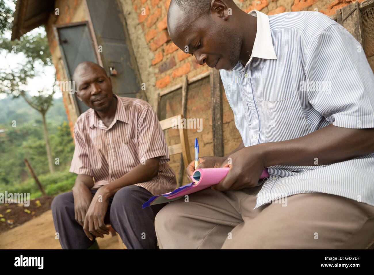 A micro-processing station manager issues payment to a coffee farmer after harvesting and delivery of his coffee - Stock Image