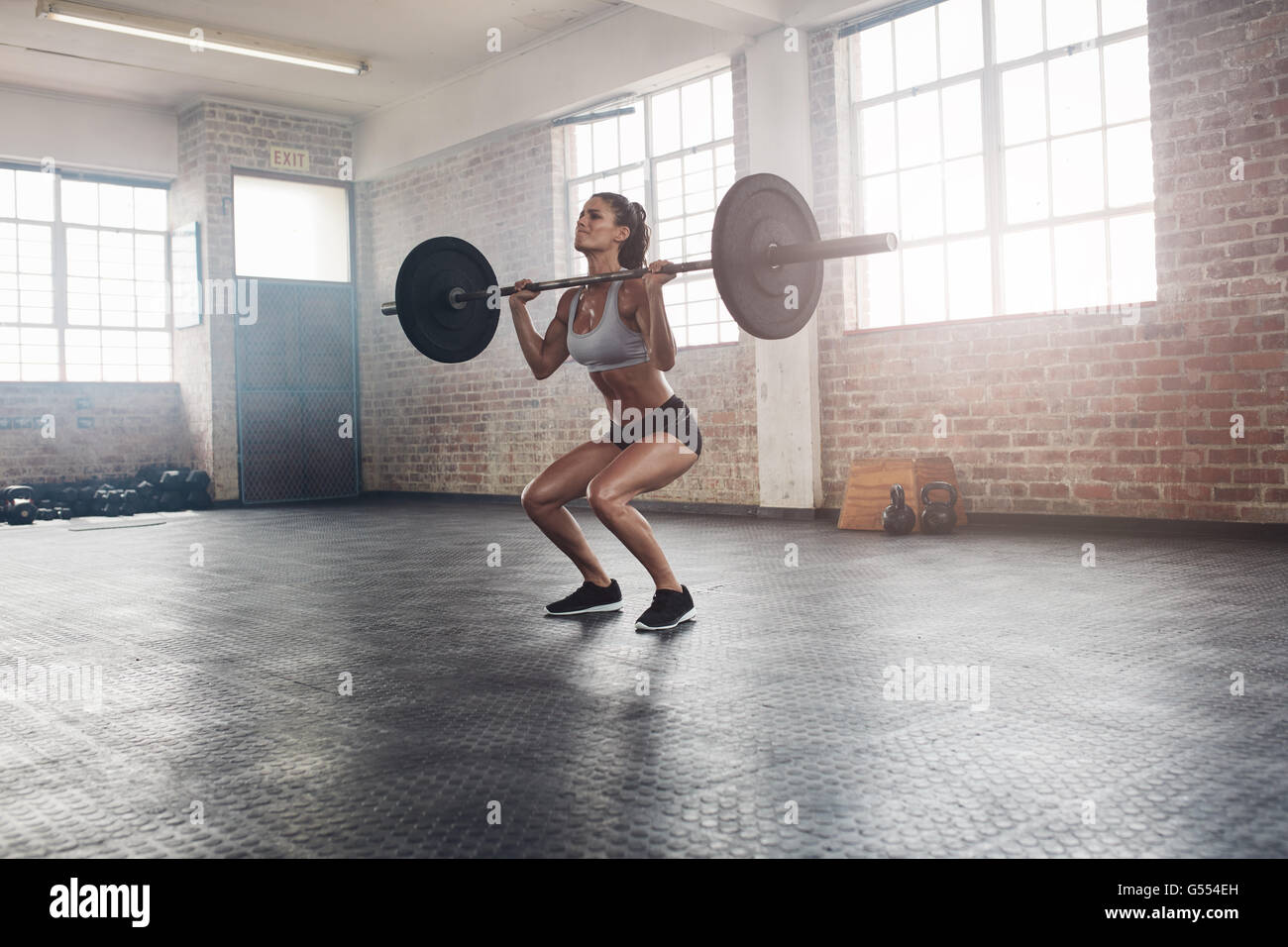 Female bodybuilder doing exercise with a heavy weight bar in gym. Full length shot of fitness woman practicing weightlifting - Stock Image