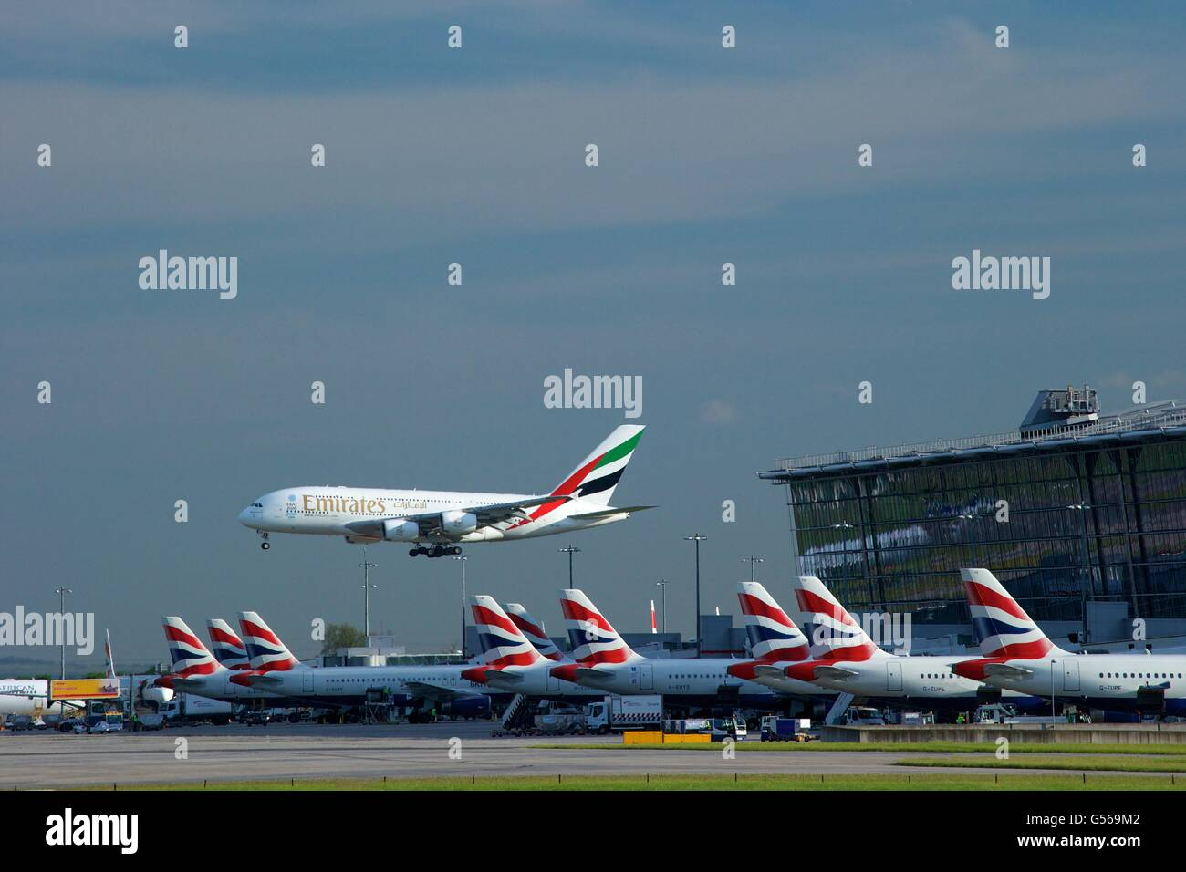 Emirates flight landing at Heathrow Airport with Terminal 5 behind, London, England, UK, GB, - Stock Image