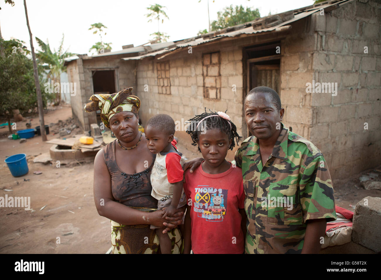 A family stands together outside their house in Nampula, Mozambique. - Stock Image