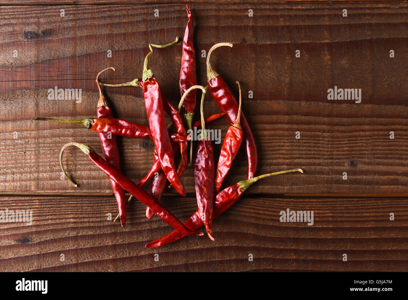 Dried Chili Still Life. Horizontal format on a rustic wood table with copy space. - Stock Image