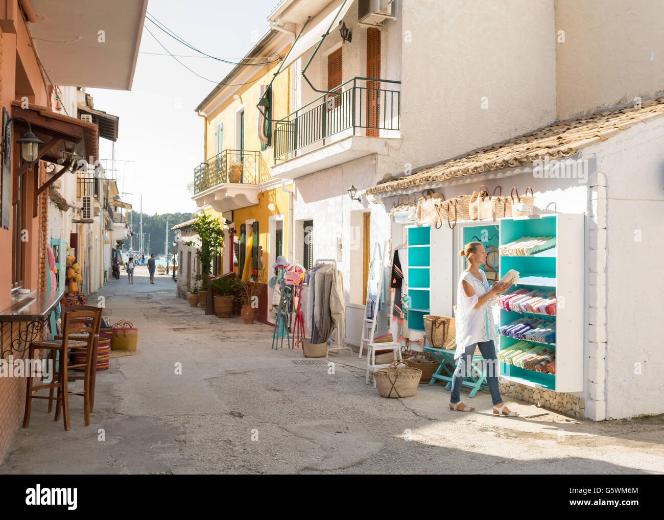 Lakka, Paxos, Greece - young woman setting up her shop selling clothing and accessories Stock Photo
