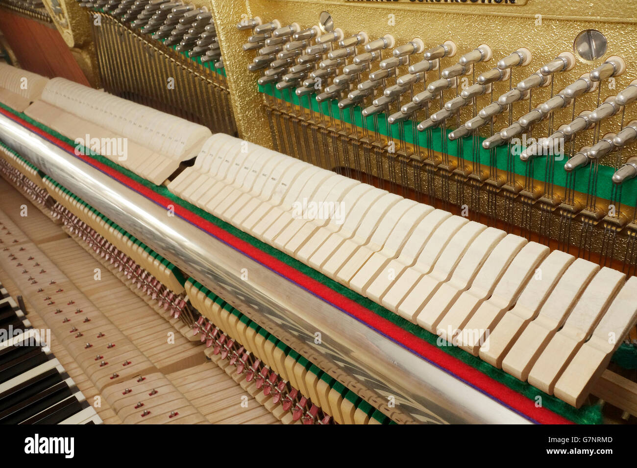Diagonal view of an upright piano action mechanism. Keyboard, hammer rail, hammers and tuning pins on pin block - Stock Image