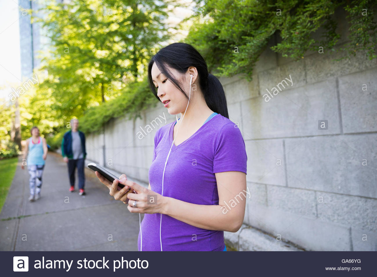 Pregnant woman with headphones using cell phone on city sidewalk - Stock Image