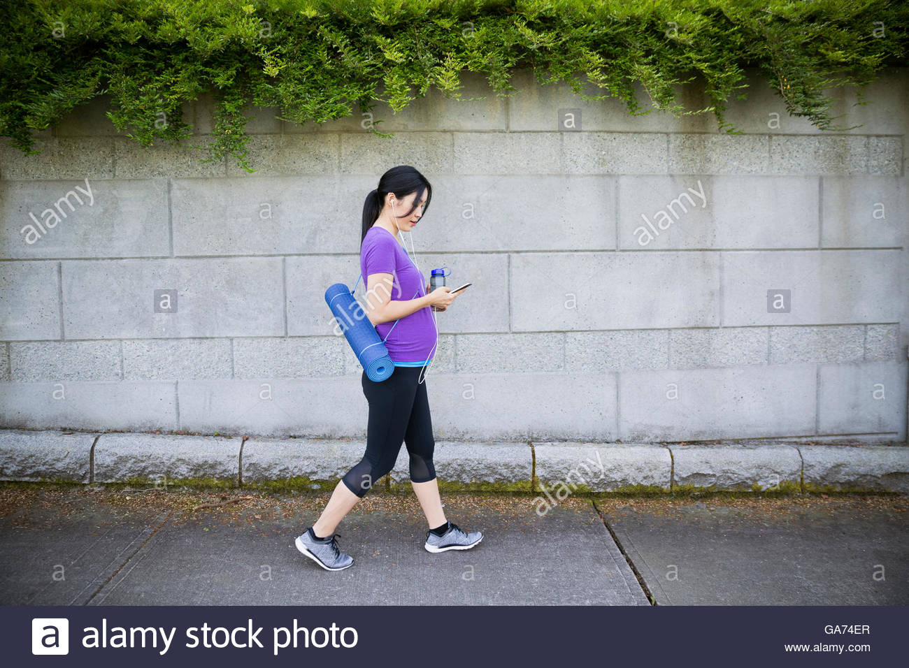 Pregnant woman with yoga mat and headphones using cell phone on sidewalk - Stock Image