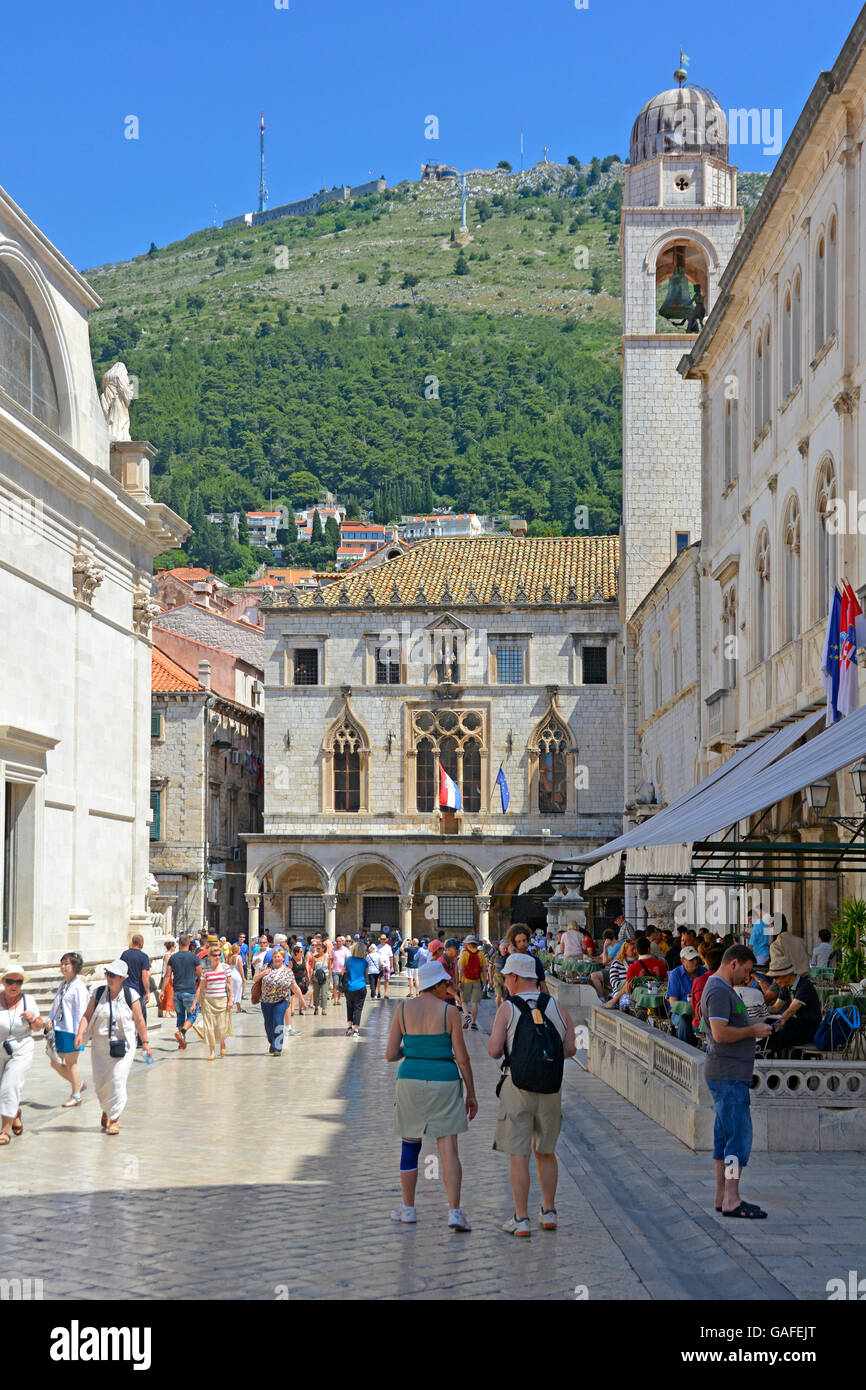 Street scene of tourists in the Old Town in Dubrovnik Croatia with the Sponza Palace and Bell Tower in Luza Square - Stock Image