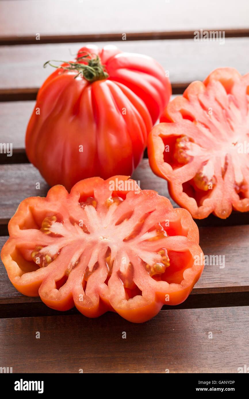 Coeur De Boeuf. Beefsteak tomatoes on wooden table. - Stock Image