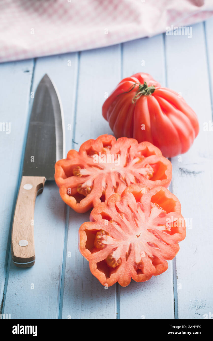 Coeur De Boeuf. Beefsteak tomatoes and knife on kitchen table. - Stock Image
