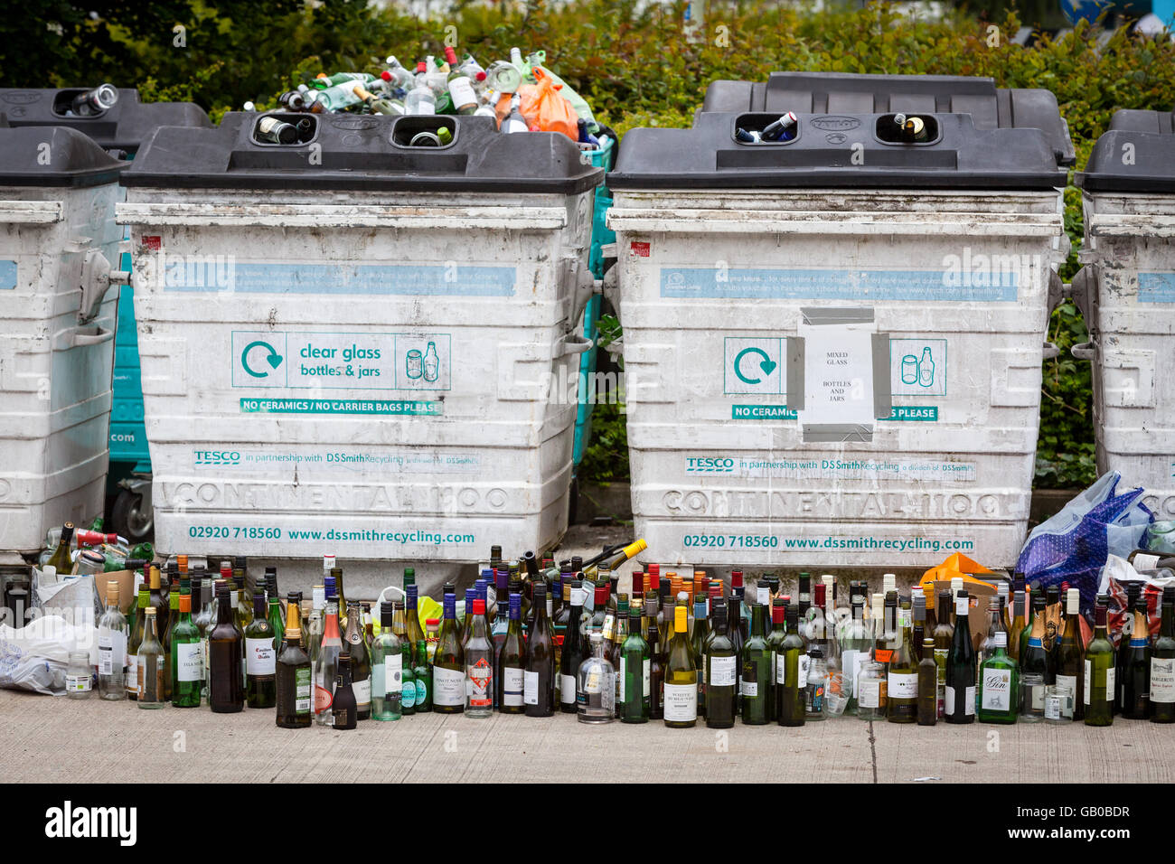 Overflowing recycling glass bottle bank in Winchester, UK with rows of wine bottles lined up in front - Stock Image
