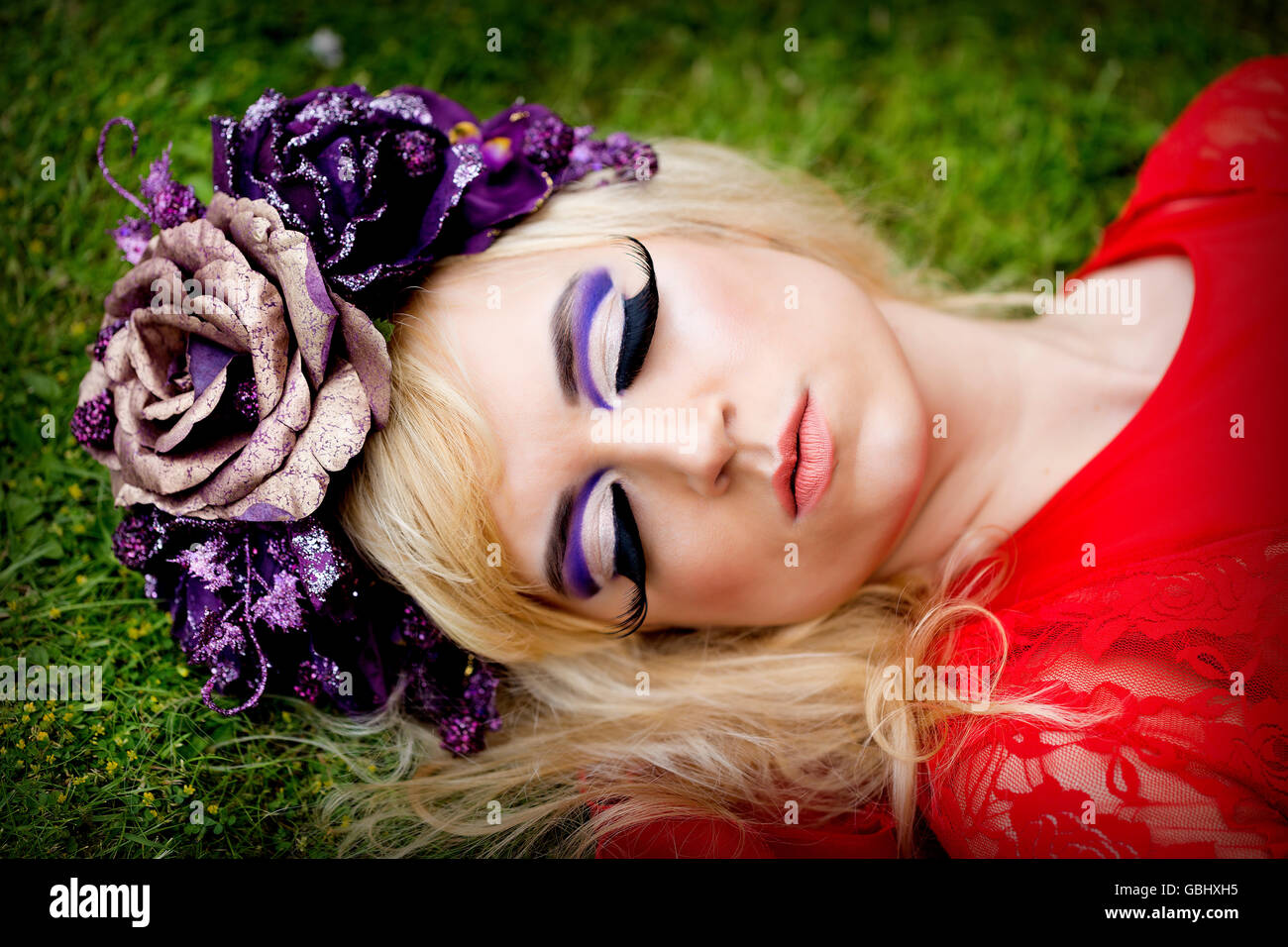 Blonde model delicate features purple flower crown winged stock blonde model delicate features purple flower crown winged eyeliner huge eyelashes red lace dress lying sleeping on grass izmirmasajfo Images