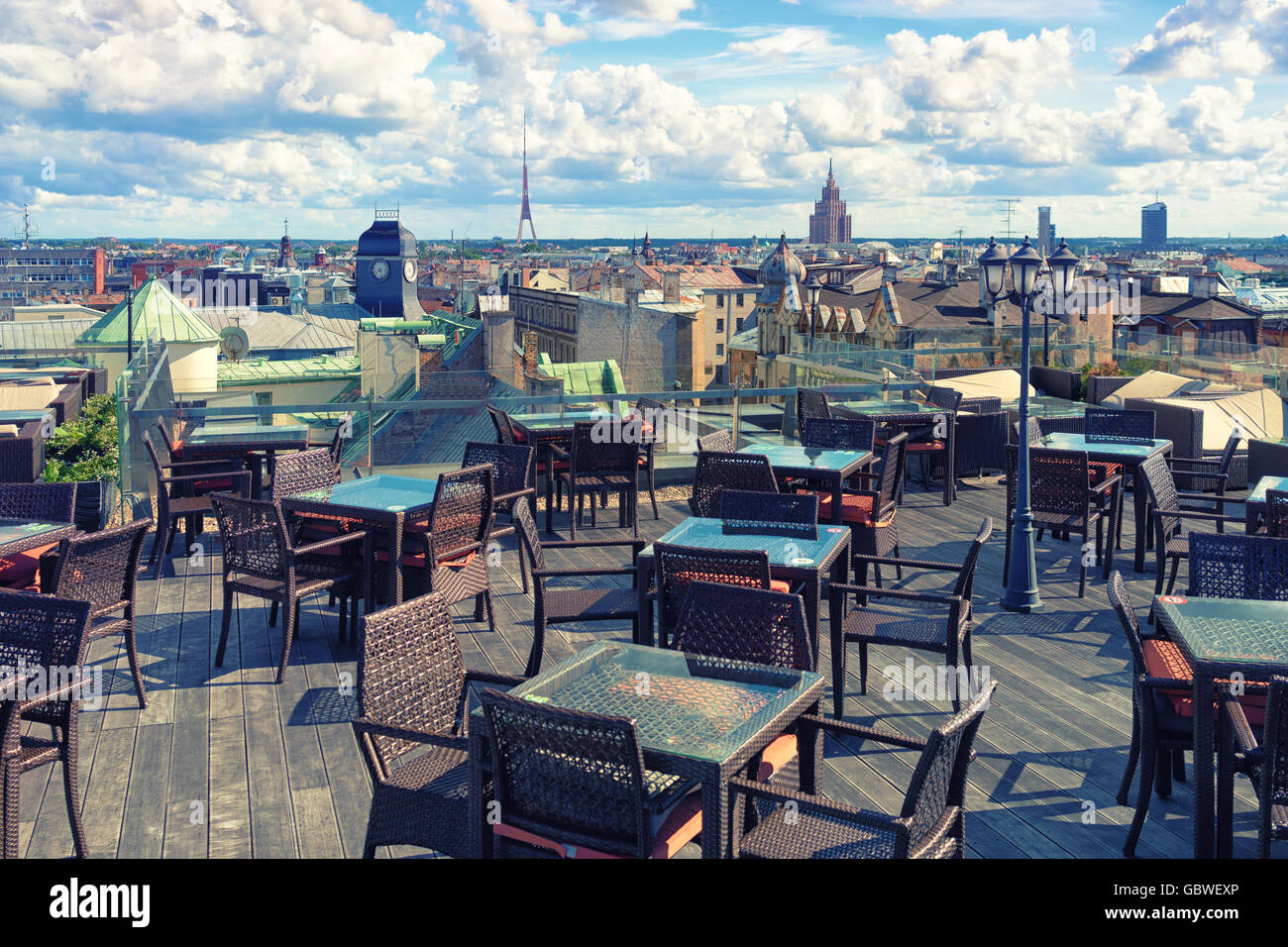 Cafe tables on the terrace roof of the building with views of the towers and skyscrapers in the city of Riga with - Stock Image