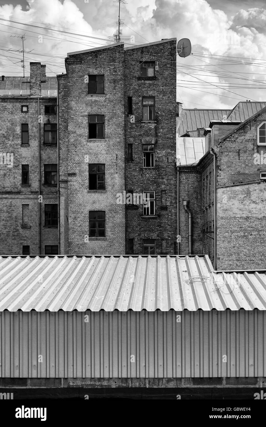 Monochrome graphical view of the old house and clouds with an iron corrugated roof in the foreground - Stock Image